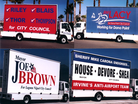 An Image of Multiple Mobile Billboards Of Political Campaigns.
