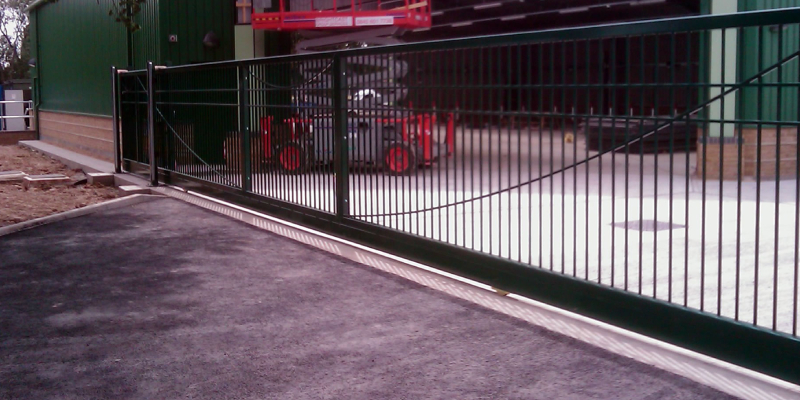 Neatly designed long sliding gate in front of a factory.