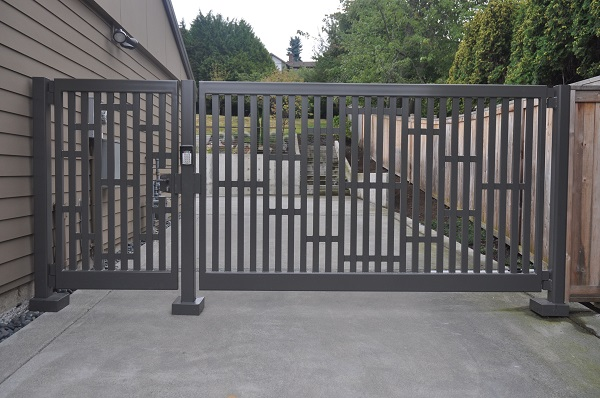 Grey coloured swing gate at the side of the countryside house.
